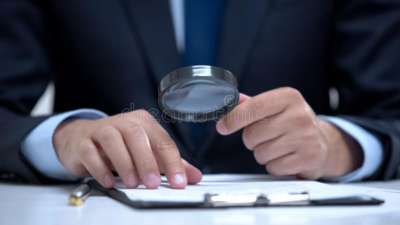 Attorney reading document with magnifier, studying case in detail, investigation stock image