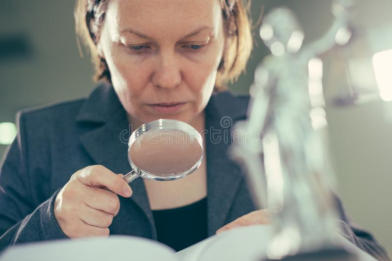 Attorney woman using magnifying glass for law book reading stock images