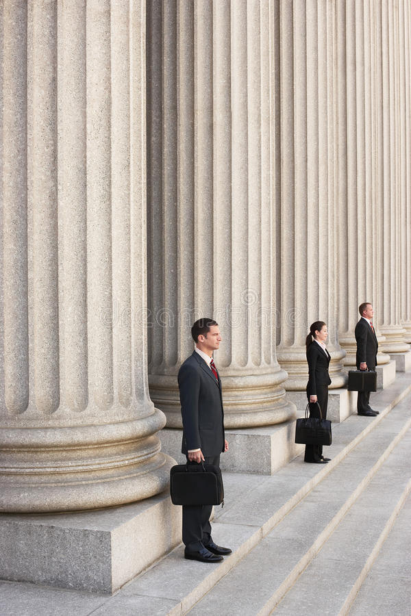 Attorneys Waiting On Courthouse Steps. Full length side view of three attorneys waiting on courthouse steps royalty free stock photos