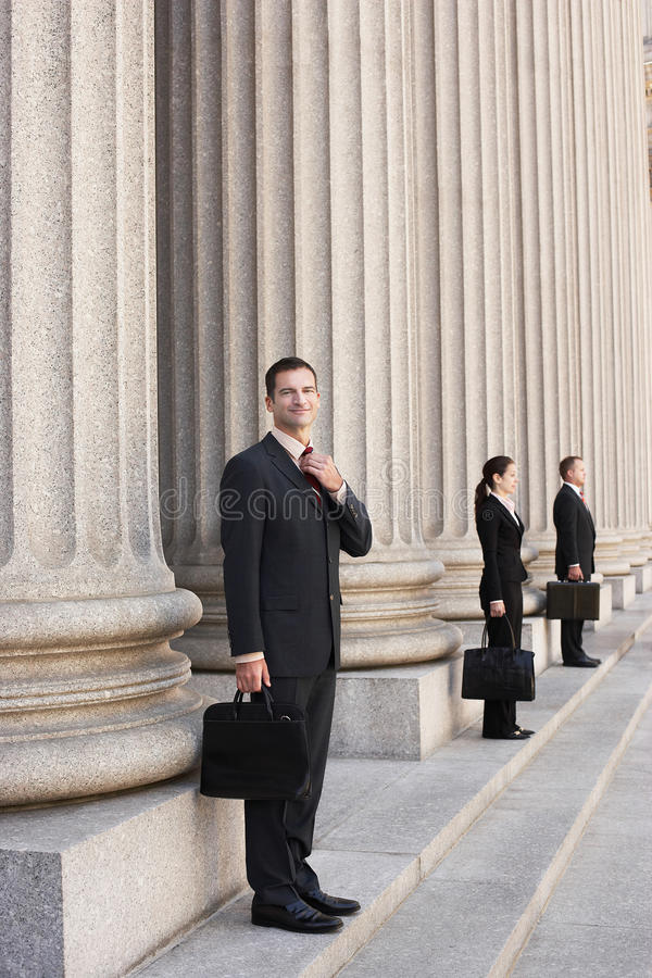 Attorneys Waiting On Courthouse Steps. Full length side view of three attorneys waiting on courthouse steps royalty free stock images