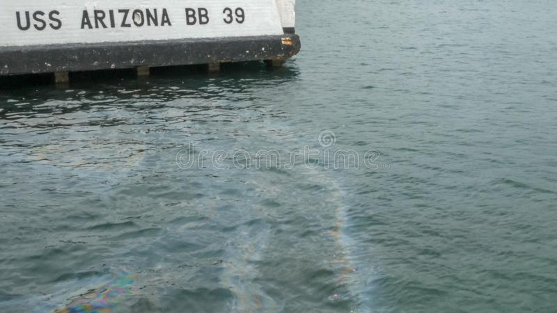 Attracco per i uss Arizona e uno splendore dell'olio sulla superficie dell'acqua immagini stock