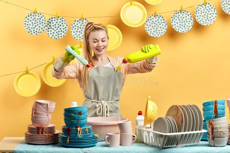Attracive令人敬畏的年轻女人混合的洗碗盘行为肥皂用水 免版税库存图片