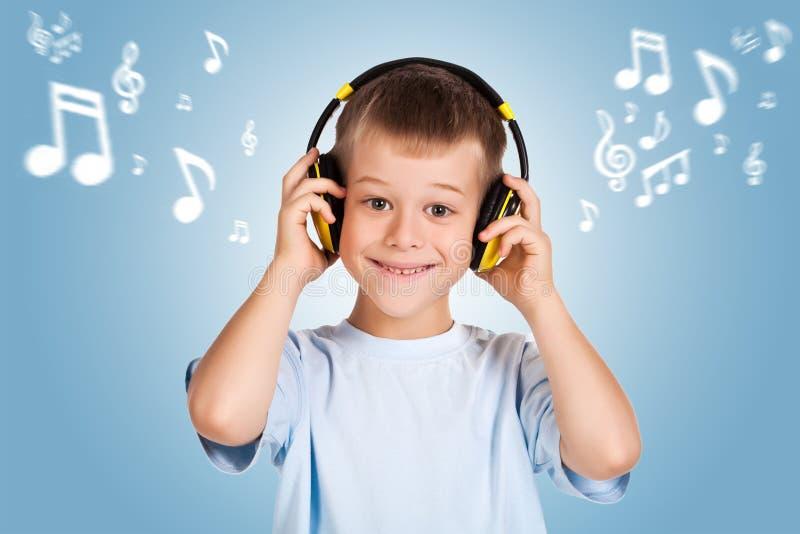 Attracive孩子是与耳机的听的音乐 图库摄影