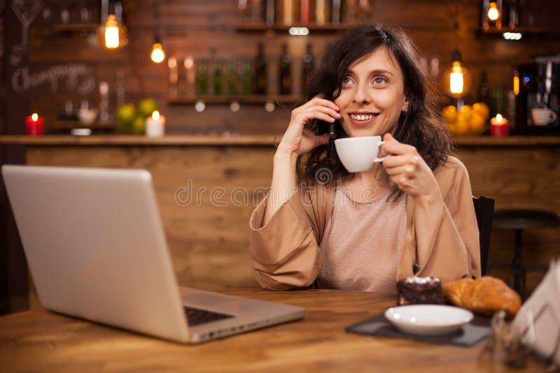 Attracive年轻女商人饮用的咖啡和有电话在一现代咖啡馆 库存图片