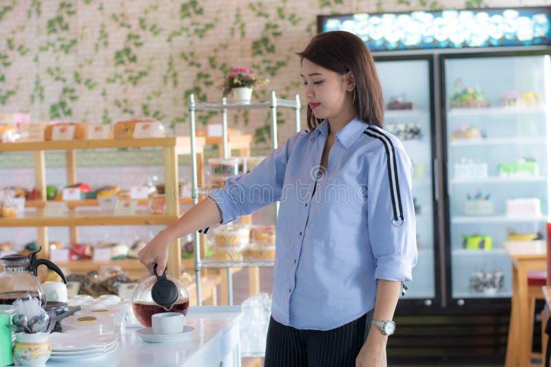 Attracive Aziatische vrouwelijke gietende kop van koffie van koffiezetapparaatketel bij cake stock foto