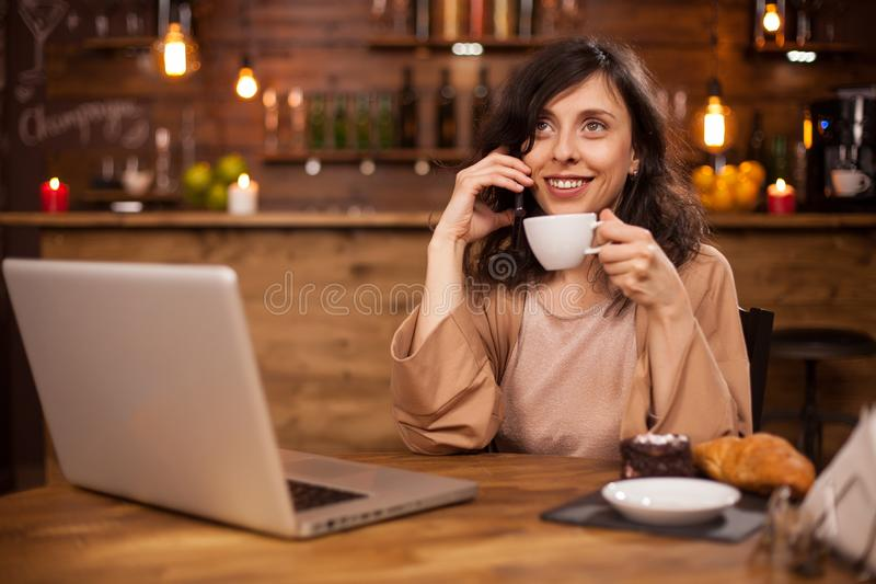 Attracive jonge het bedrijfsvrouw drinken koffie en het hebben van een telefoongesprek in een moderne koffiewinkel stock afbeelding