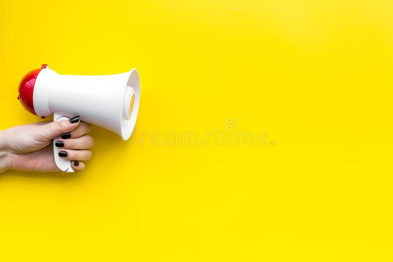 Attract attention concept. Megaphone in hand on yellow background top view copy space. Attract attention concept. Megaphone in hand top view copy space stock photo