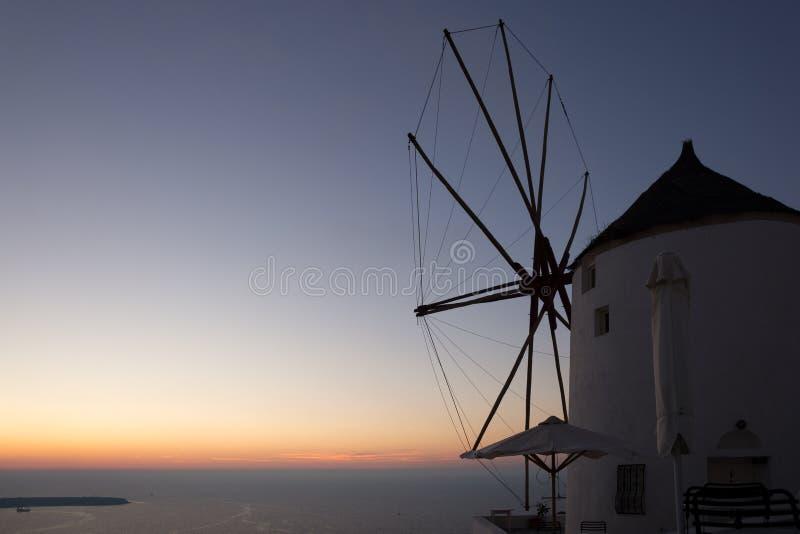Attraction célèbre de village d'Oia au coucher du soleil avec le moulin à vent en île de Santorini photos stock