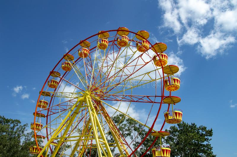 Attraction ferris wheel with red and eyllow booths. Festival, holiday, color, park, sky, summer, travel, fun royalty free stock photos