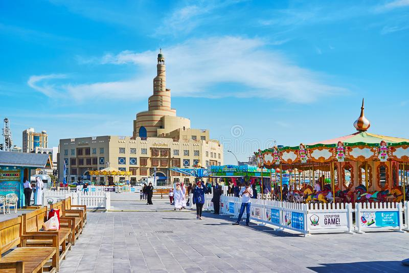 Attractions for kids in Doha, Qatar. DOHA, QATAR - FEBRUARY 13, 2018: The street of Al Souq district with carousels of Luna park and the scenic building of Al stock image