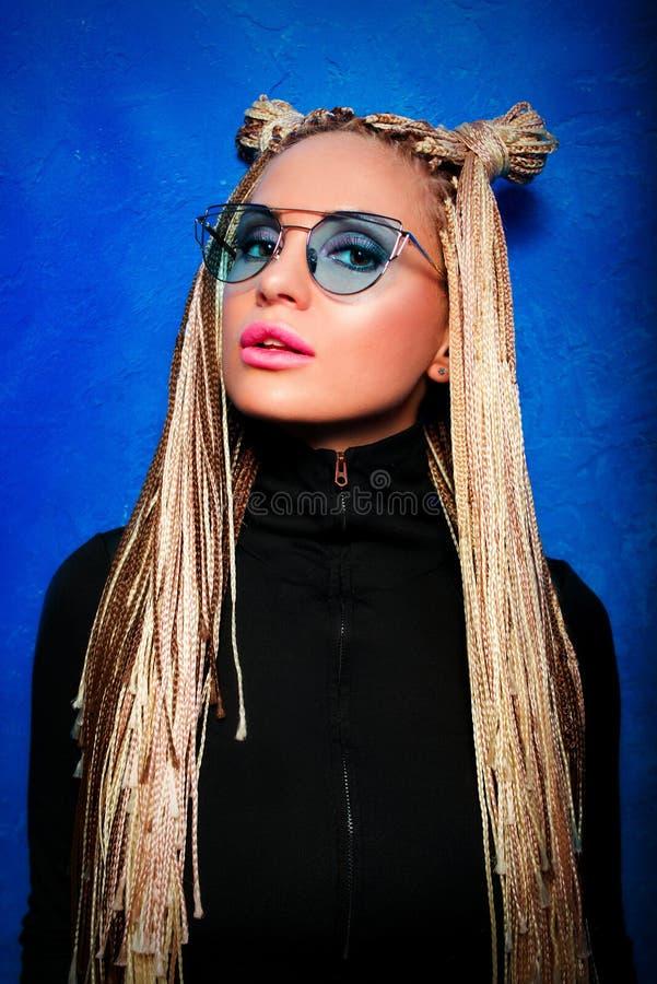 Attractiva-younge Blondine mit afrikanischen Zöpfen im schwarzen Pullover lizenzfreie stockbilder