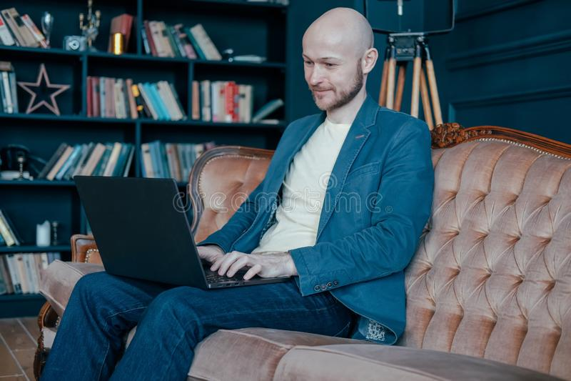 Attractive adult successful smiling bald man with beard in suit working at laptop on his rich cabinet stock image