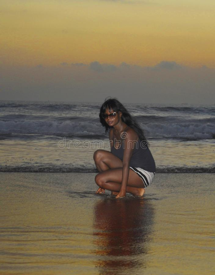 Attractive african american black woman walking on sunset beach enjoying water and sand relaxed royalty free stock image