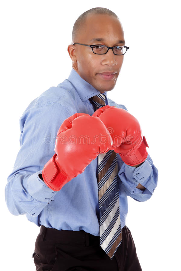 Attractive African American businessman. Attractive young African American businessman wearing boxing gloves. Blow with right arm. Studio shot. White background stock photo