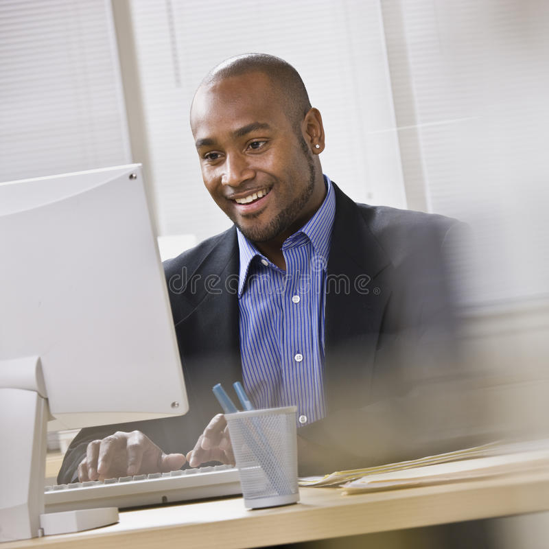 Attractive African American at computer. stock photos