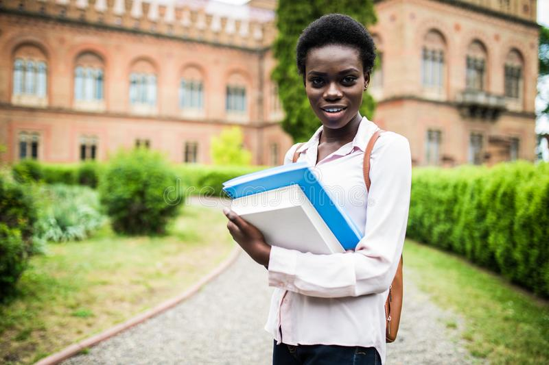 Campus life. Young attractive african American female college student on campus. royalty free stock images