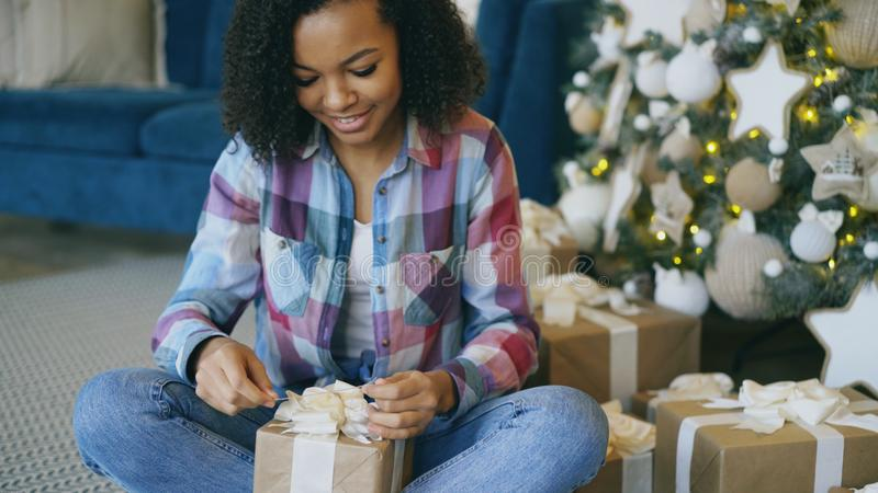 Attractive mixed race girl packing gift box near Christmas tree at home stock photo