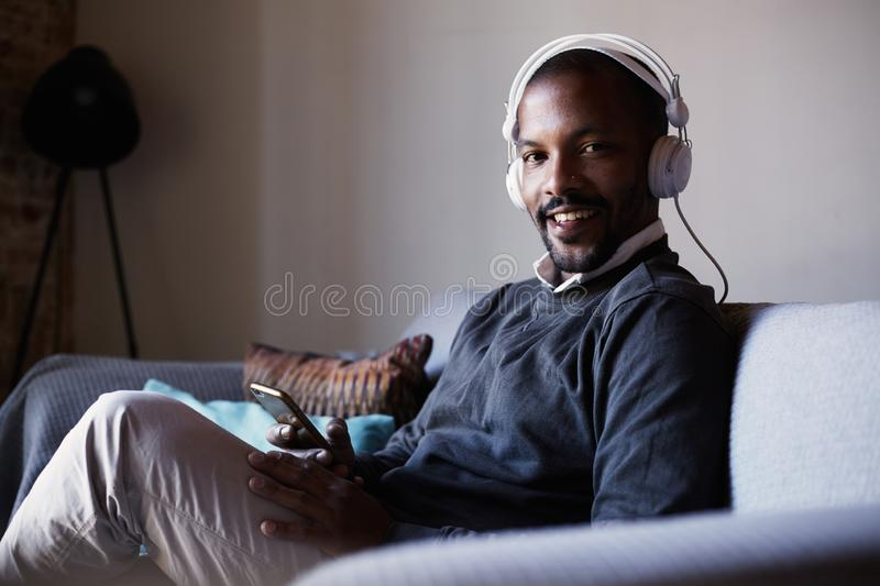 Attractive African American man with white headphones listening to music on his phone. Concept of relaxation. stock photography