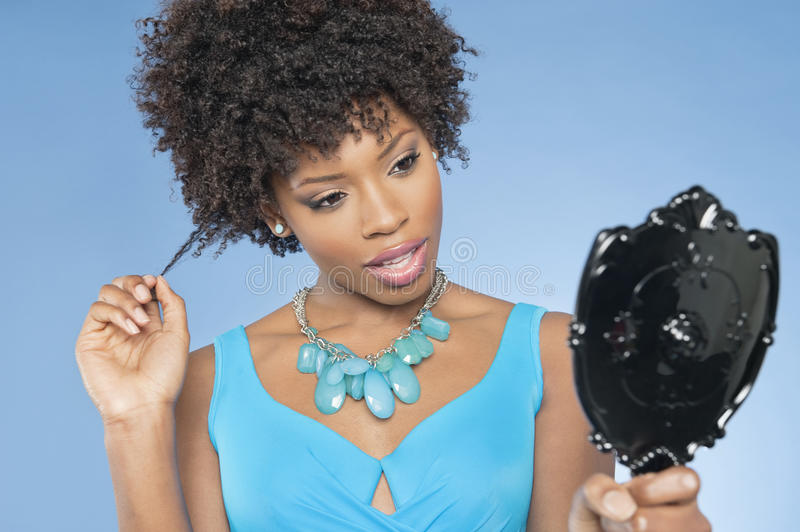 Attractive African American woman looking at herself in mirror over colored background royalty free stock photography