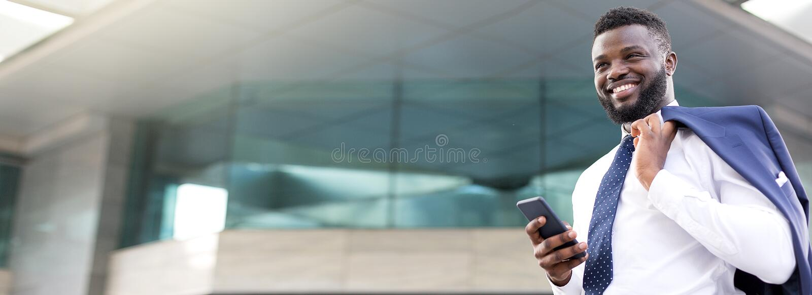 Attractive african businessman holding his phone while standing near a storey building and looking straight ahead stock photos