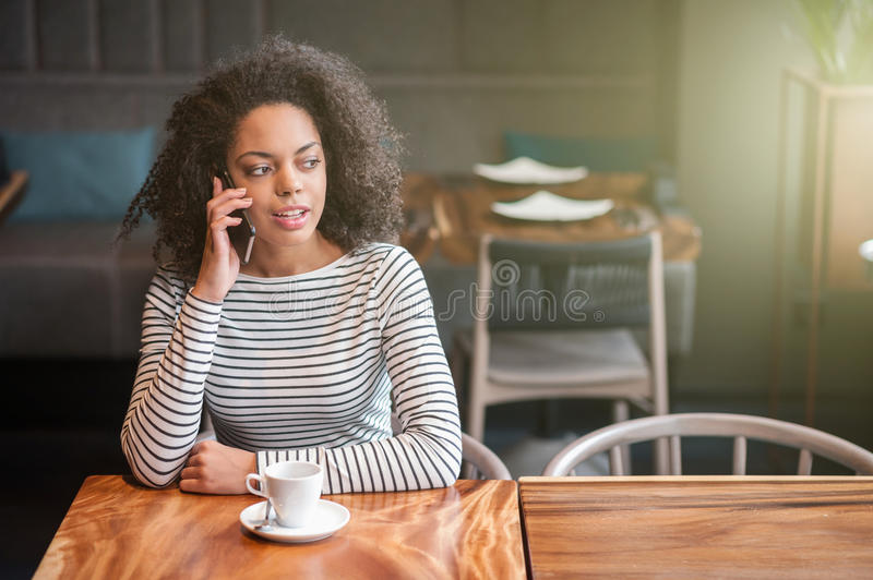 Attractive african girl is communicating on telephone. Beautiful young woman is talking on the mobile phone. She is sitting at table in cafe and smiling stock photos