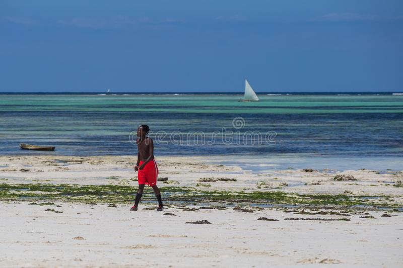 An attractive African men standing on the beach on background of blue sky and ocean.Seascape of an african coast. royalty free stock images