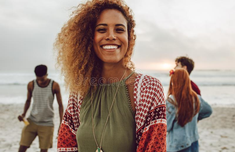 Attractive african woman on the beach. Attractive african women on the beach smiling at camera. Pretty young female standing at the beach with group of friends royalty free stock image