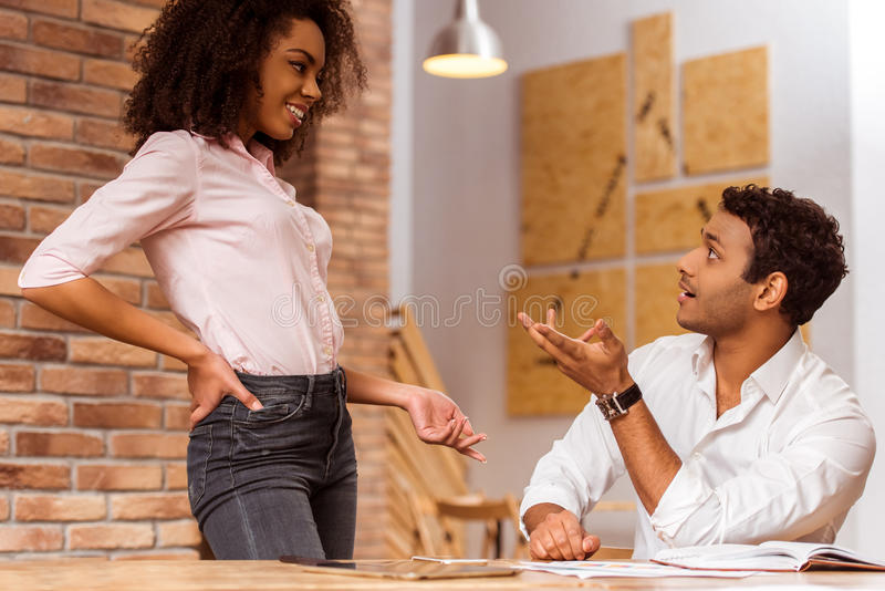 Attractive Afro-American couple working. Young attractive Afro-American business couple talking while working in cafe royalty free stock photos