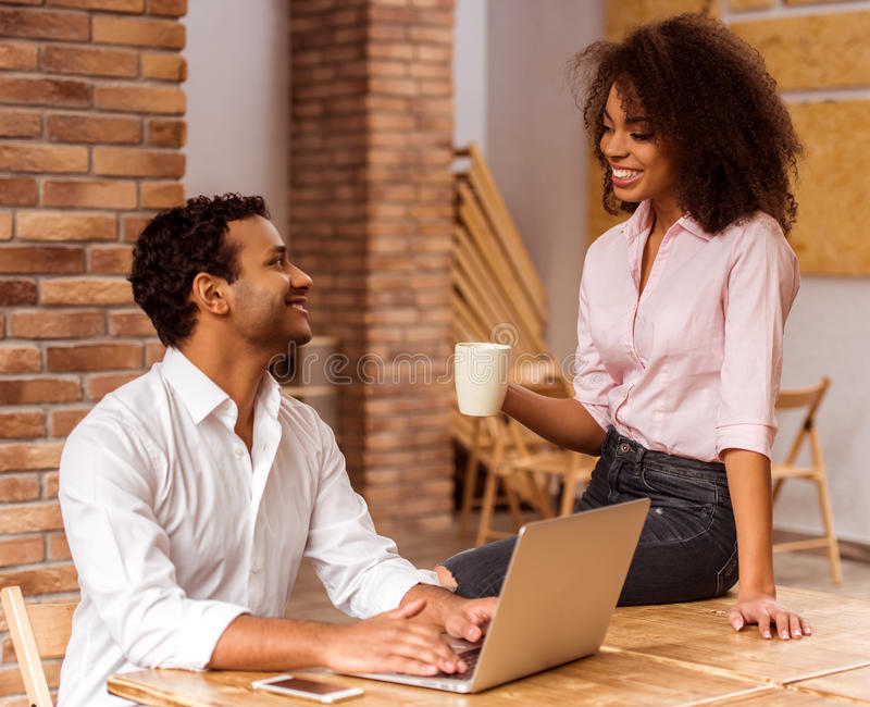 Attractive Afro-American couple working. Young attractive Afro-American business couple talking and smiling while working in cafe. Man using laptop. Woman stock photo