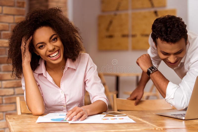 Attractive Afro-American couple working. Young attractive Afro-American business couple using laptop and laughing while working in cafe royalty free stock photography
