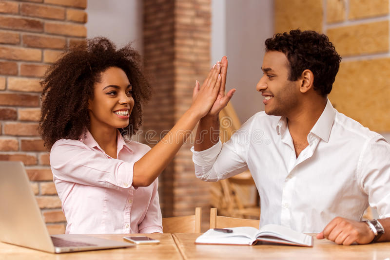 Attractive Afro-American couple working. Young attractive Afro-American business couple using laptop, making notes, giving high five and smiling while working in stock photography