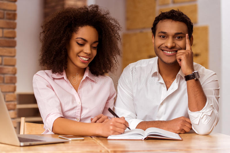 Attractive Afro-American couple working. Young attractive Afro-American business couple using laptop, making notes and smiling while working in cafe royalty free stock photo