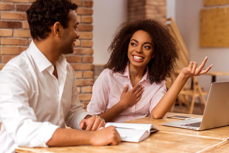 Attractive Afro-American couple working. Young attractive Afro-American business couple using laptop, making notes, talking and smiling while working in cafe stock image