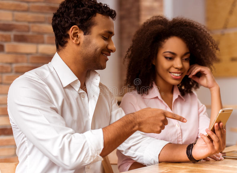 Attractive Afro-American couple working. Young attractive Afro-American business couple using smart phone, talking and smiling while working in cafe royalty free stock photos