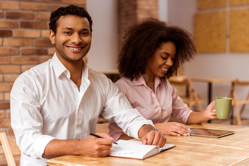 Attractive Afro-American couple working. Young attractive Afro-American business couple using tablet, drinking tea, making notes and smiling while working in royalty free stock image
