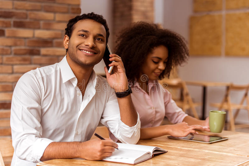 Attractive Afro-American couple working. Young attractive Afro-American business couple using tablet, drinking tea, making notes, talking on the phone and royalty free stock photography
