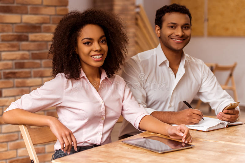 Attractive Afro-American couple working. Young attractive Afro-American business couple using tablet, making notes, looking in camera and smiling while working stock photo