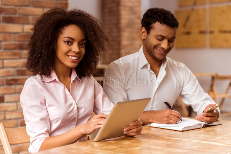 Attractive Afro-American couple working. Young attractive Afro-American business couple using tablet, making notes, looking in camera and smiling while working stock photos