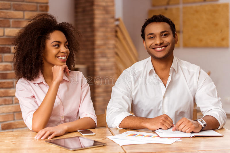 Attractive Afro-American couple working. Young attractive Afro-American business couple using tablet, making notes, looking in camera and smiling while working royalty free stock image