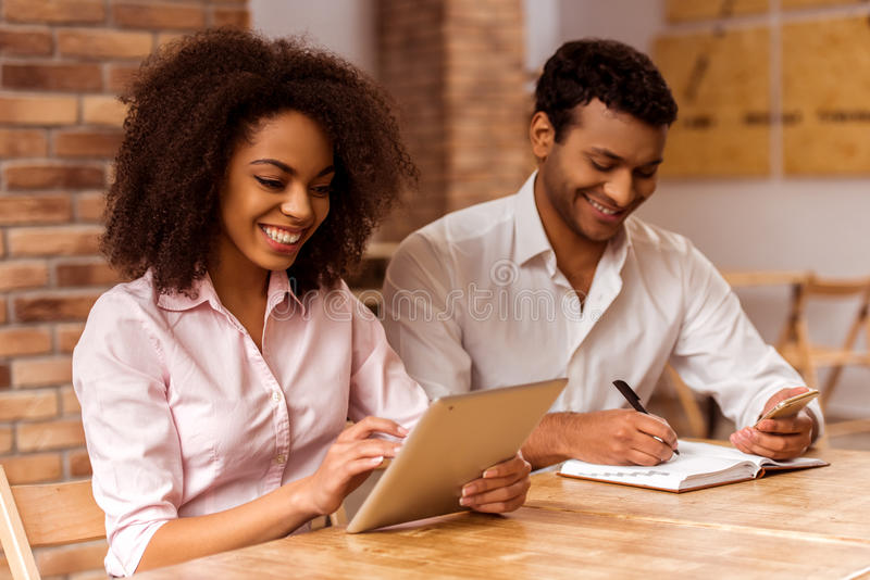 Attractive Afro-American couple working. Young attractive Afro-American business couple using tablet, making notes and smiling while working in cafe royalty free stock photography