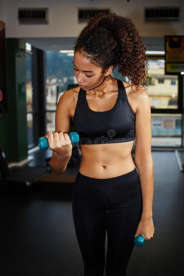 Attractive afro american girl lifting dumbbells at gym stock images