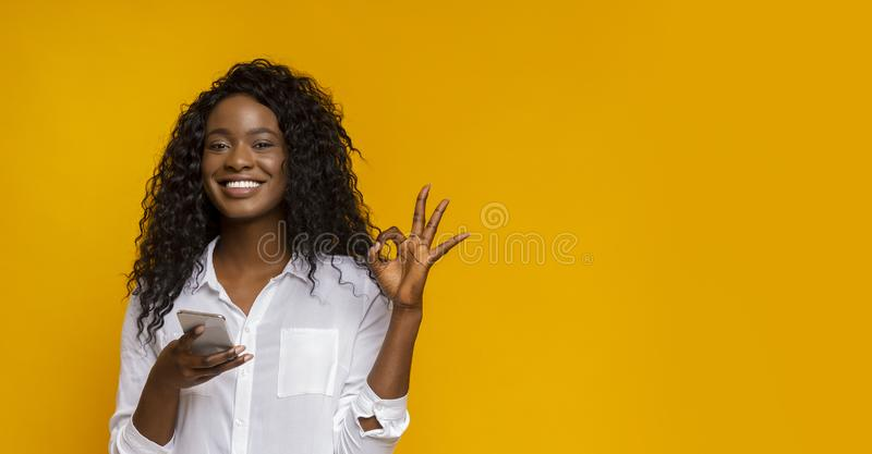 Attractive afro girl showing her satisfaction with new application royalty free stock photos