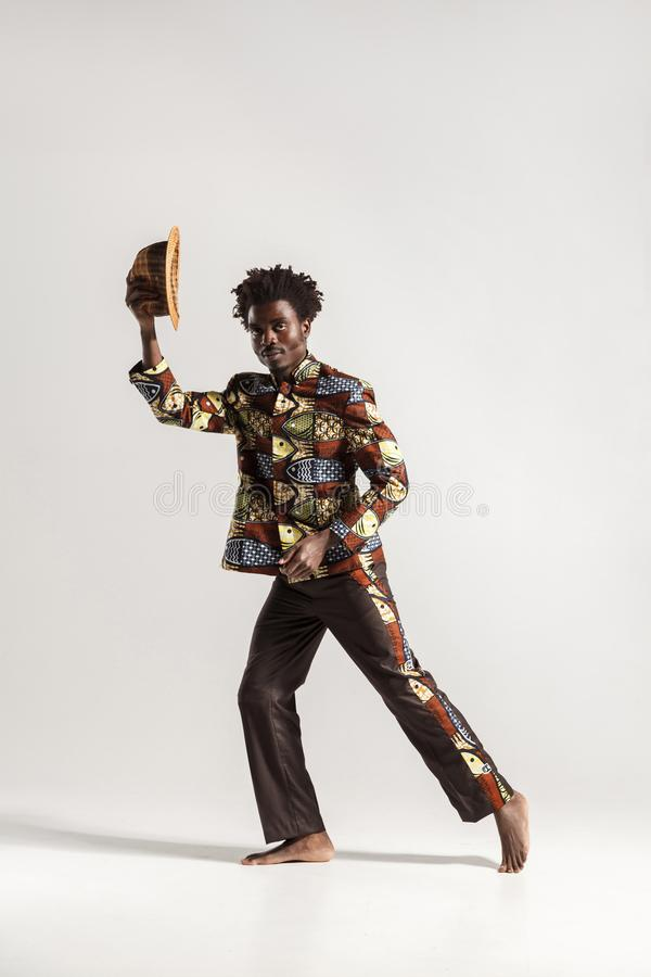 Attractive afro man holding hat and looking at camera stock photo