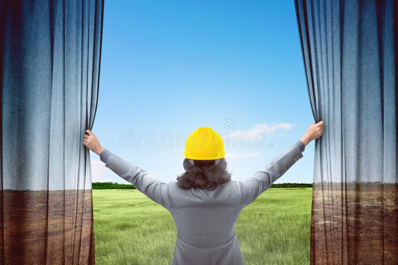 Attractive architect woman opening curtains and looking green la stock images