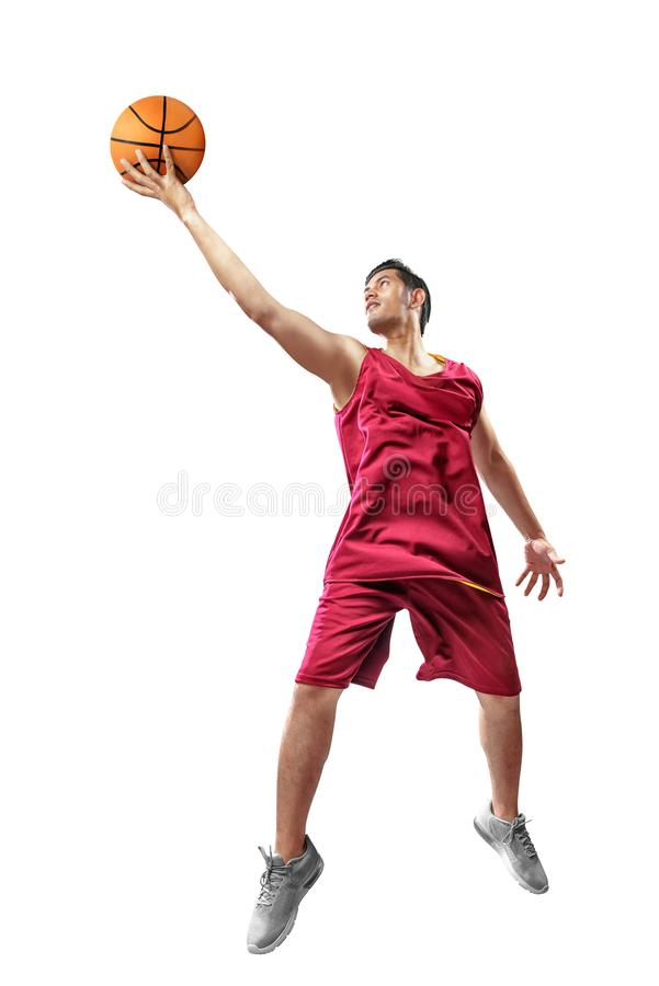 Attractive asian basketball player man in red uniform jumping with ball in hands royalty free stock image