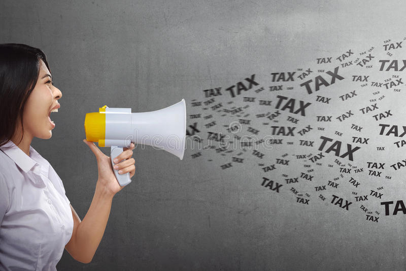 Attractive asian business woman saying taxes with megaphone. On black wall background royalty free stock photography