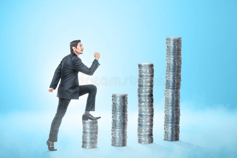 Attractive asian businessman going to the top of coins stack. Over blue background stock photos