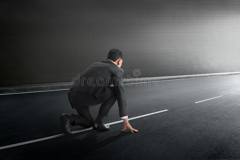 Attractive asian businessman in ready position to run. On tunnel royalty free stock images