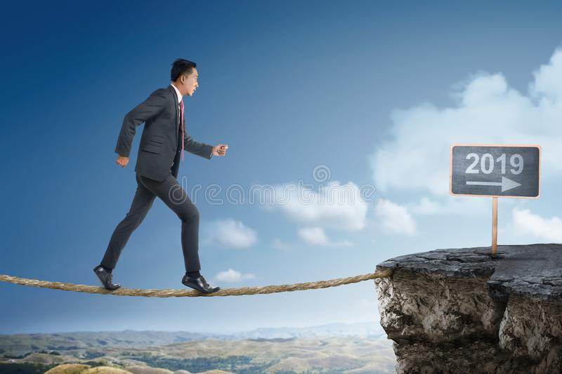 Attractive asian businessman on rope bridge walking into 2019 stock images