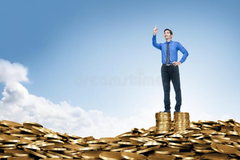 Attractive asian businessman standing on the top of coin stack. Business concept royalty free stock image